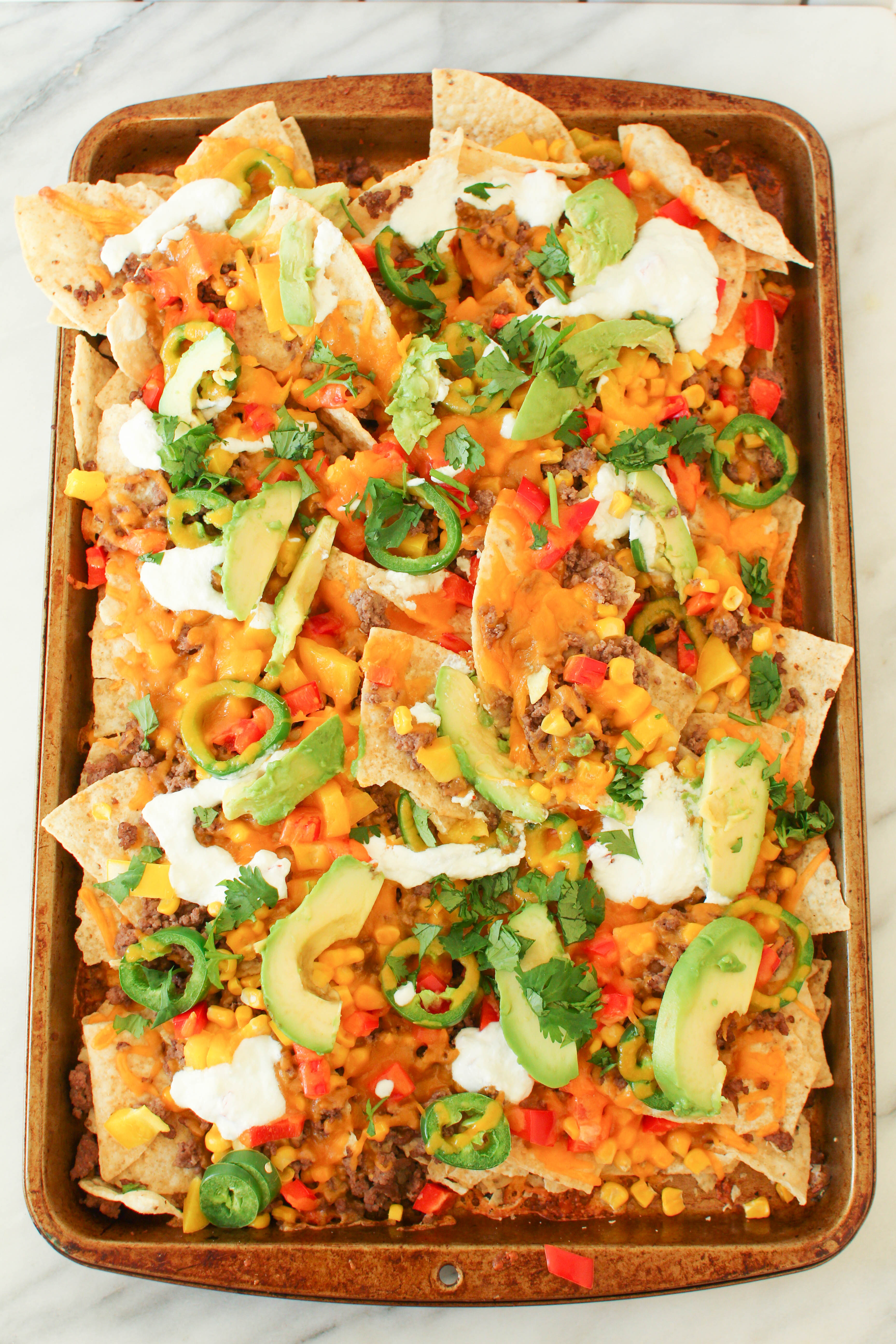 Perfect for game day, these cheesy beef sheet pan nachos can feed a crowd. Tortilla chips topped with seasoned ground beef, corn, peppers, jalapenos and cheese and baked until crispy and melted. Topped with sour cream, avocado and cilantro.