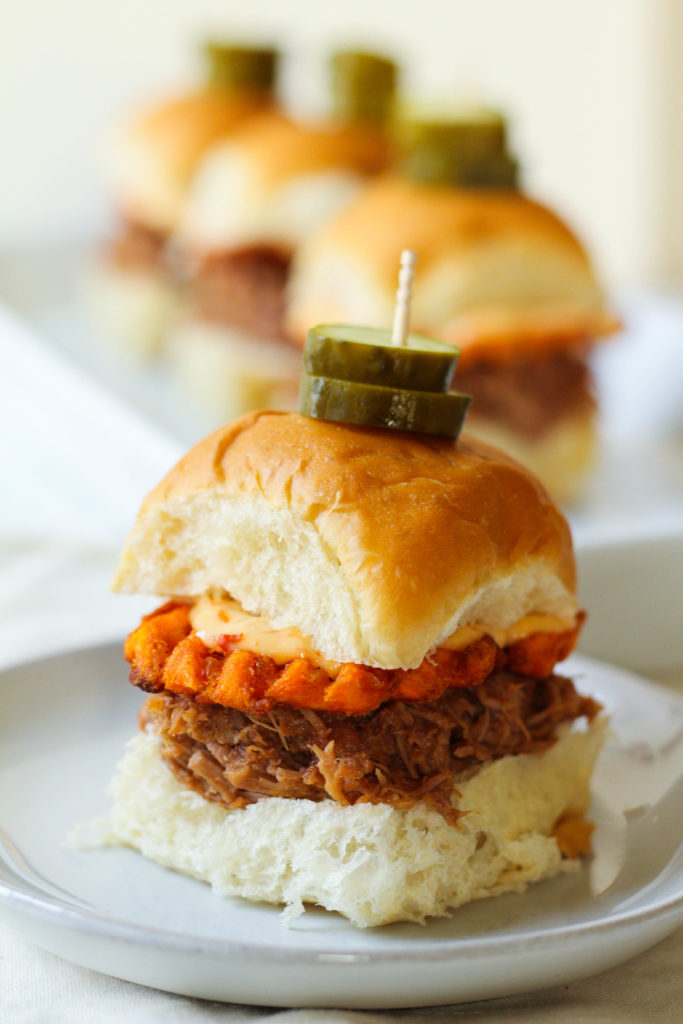 These pulled pork sliders are perfect to serve a large crowd on game day! Pressure cooked until tender and covered with a tangy and sweet barbecue sauce.