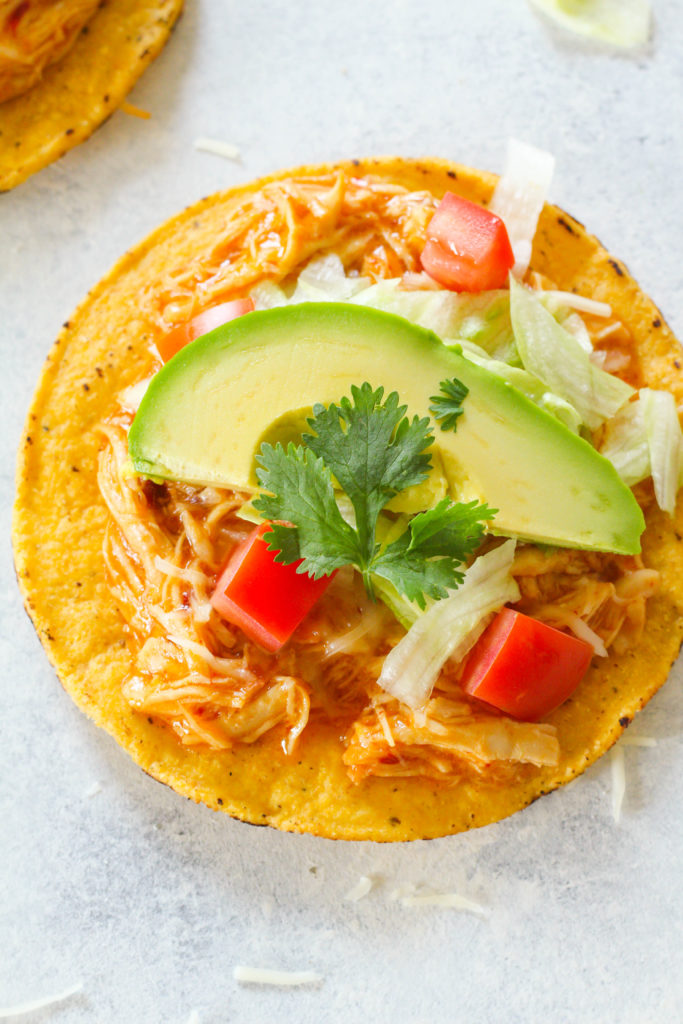 These Instant Pot Chicken Tostadas are super easy to make and perfect for your next fiesta! Covered in a sweet and spicy chipotle apricot glaze and goey melted cheese.
