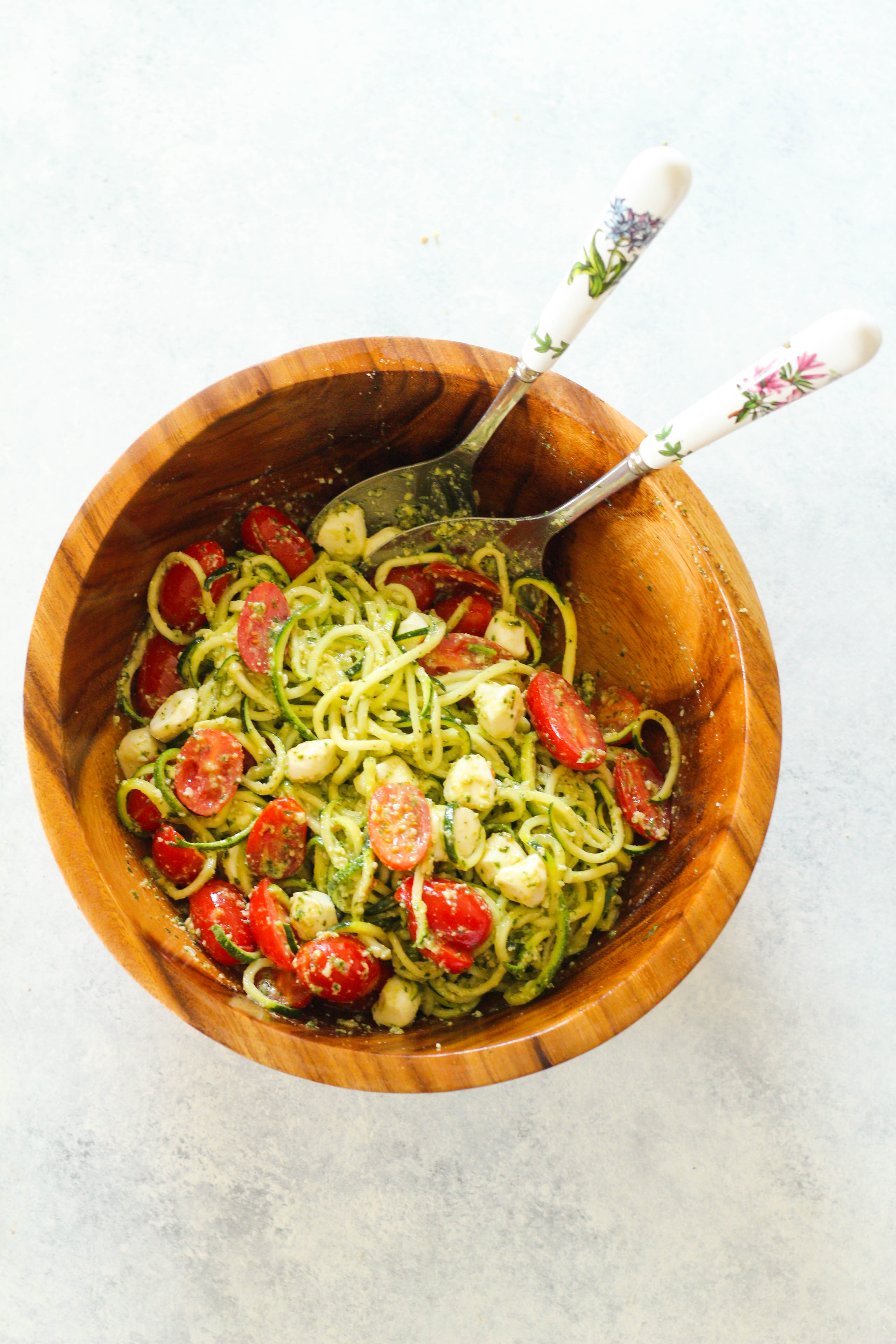 These Pesto Zucchini Noodles are a light and summery dish that doesn't require a stove top or oven! Simply whip together a fresh basil pesto and toss zucchini noodles with cherry tomatoes and mozzarella pearls.