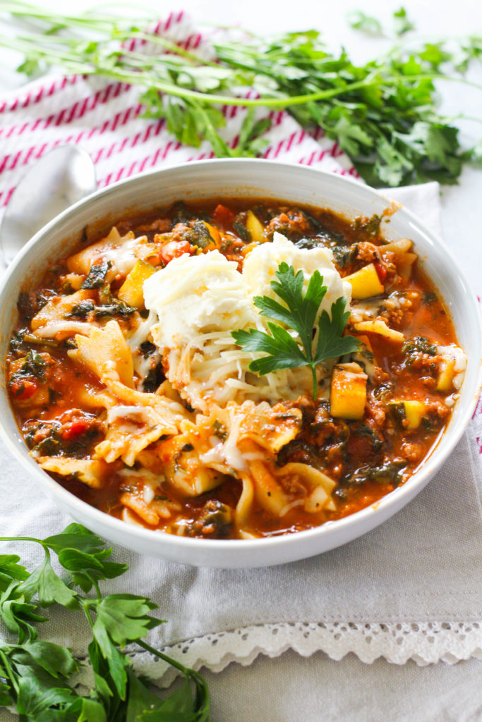 What's better than baked lasagna? Lasagna in a bowl! This Slow Cooker Lasagna Soup is packed with tender ground beef, crushed tomatoes, zucchini, spinach and bow tie pasta. Topped with a dollop of ricotta and sprinkle of mozzarella -- you've got yourself a delicious, cheesy weeknight meal!