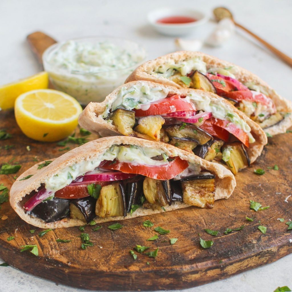 Roasted eggplant tossed in olive oil and oregano make the perfect base for these stuffed pitas! Piled high with tomatoes, pickled red onion, and dill tzatziki sauce. These roasted eggplant pitas are a delicious and vegetarian lunch option.