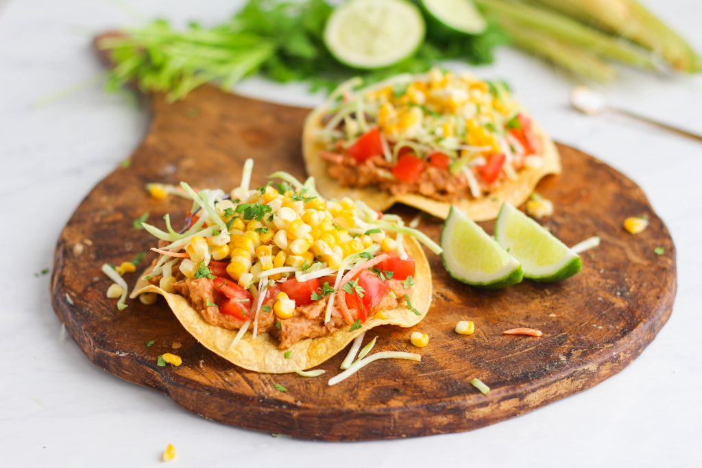 Enjoy a delicious plant based meal with these vegan Roasted Corn & Bean Tostadas! Fresh corn on the cob, roasted until brown in the oven and a creamy seasoned mashed pinto bean spread on top of a crunchy tostada shell.