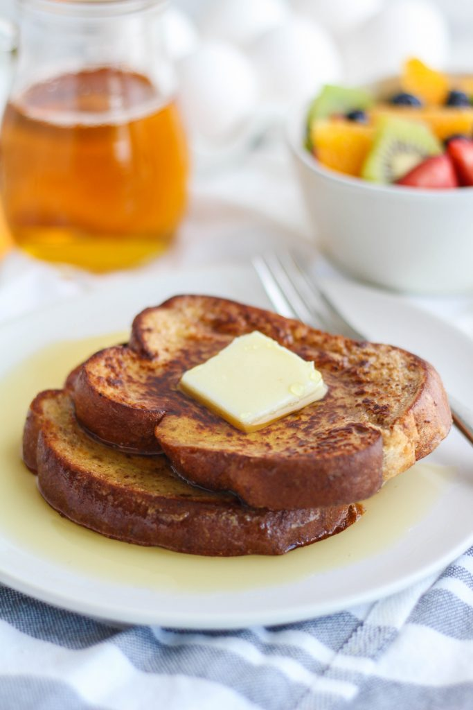 French toast slices on a white plate with a pat of butter