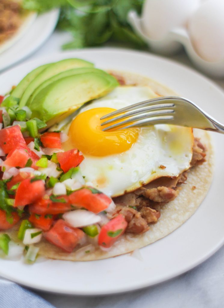 A fork slicing into an egg yolk, on a corn tortilla with pico de gallo and sliced avocado