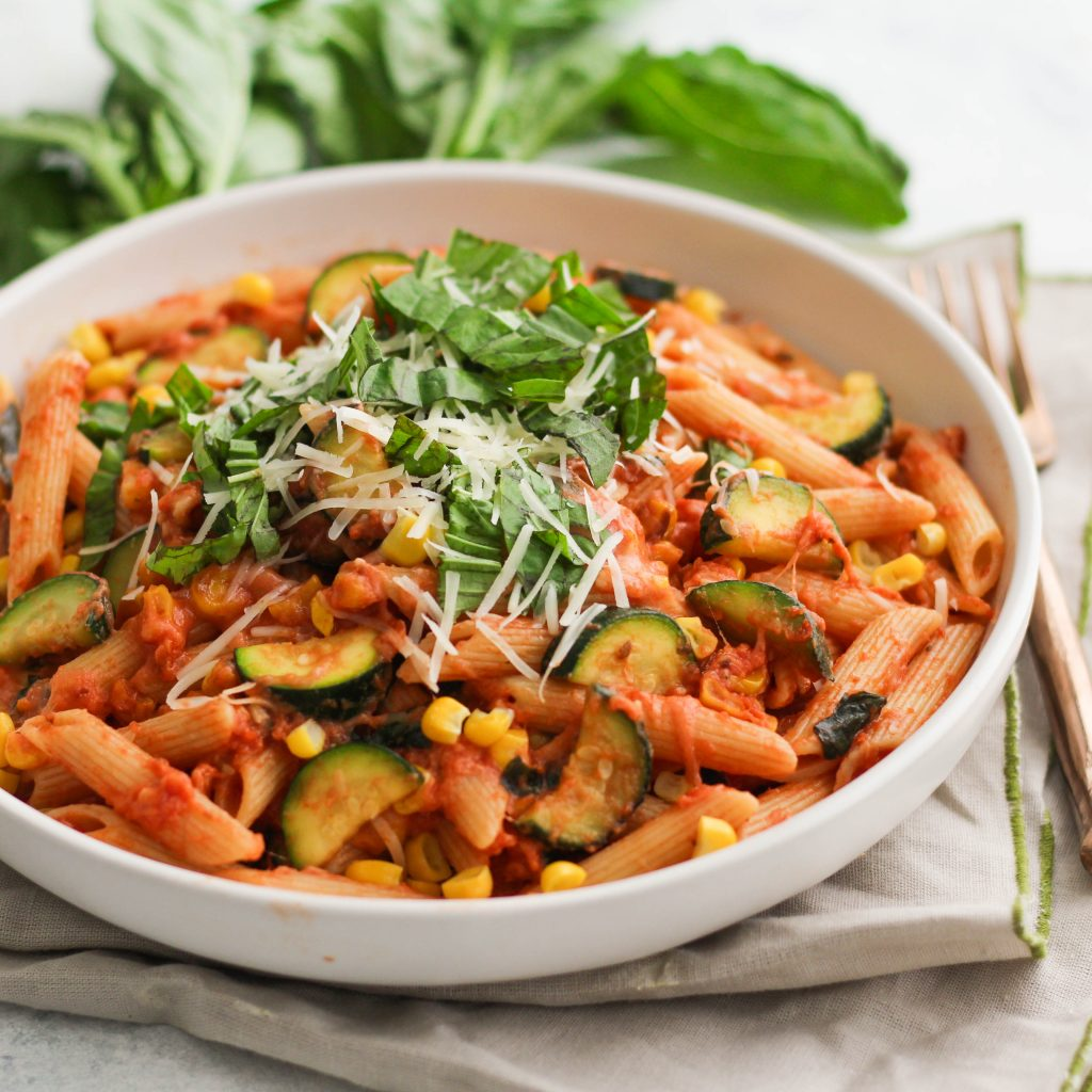 Penne pasta with tomato sauce, zucchini and corn with a pile of basil leaves