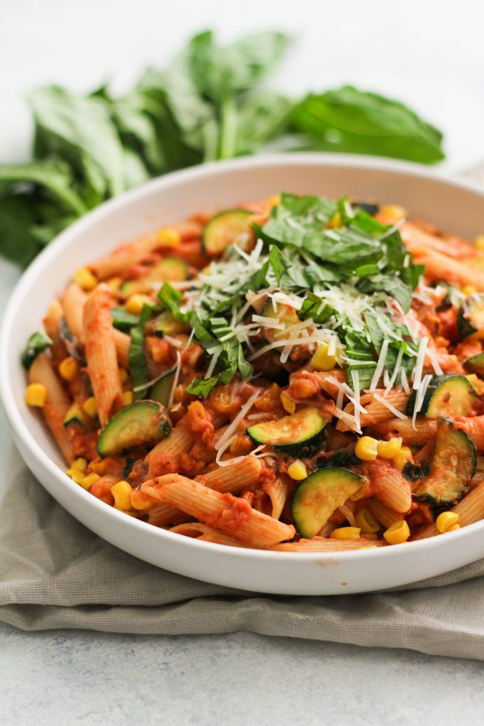 Up close shot of penne pasta with tomato sauce, zucchini, corn and fresh basil