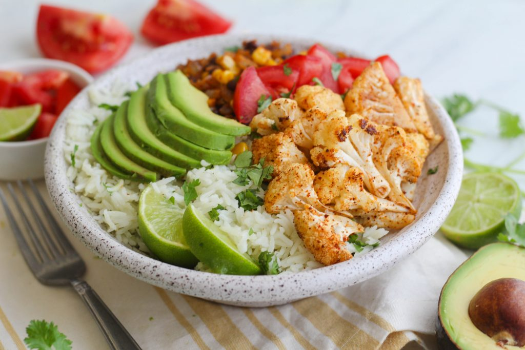 roasted cauliflower on a bed of cilantro lime rice with sliced avocado and tomatoes