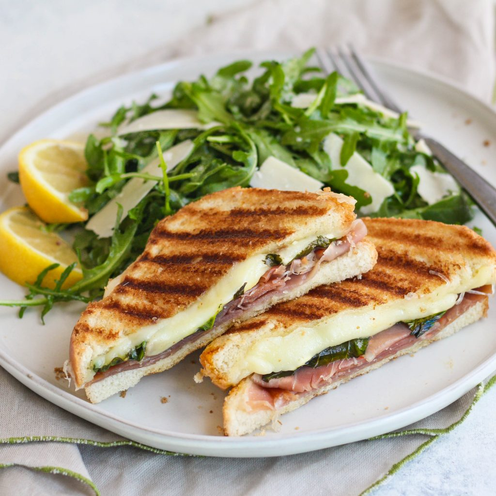 Elevate your grilled cheese with this savory mozzarella, basil, and prosciutto version! Served with a quick side salad of peppery arugula, salty Parmesan and lemon dressing.