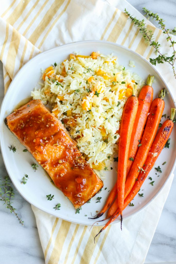 Fresh salmon topped with a homemade sweet and savory marinade consisting of fresh ginger, garlic, soy sauce, and apricot preserves. Served with a side of quick rice pilaf with dried apricots, slivered almonds, and fresh thyme, and roasted carrots.