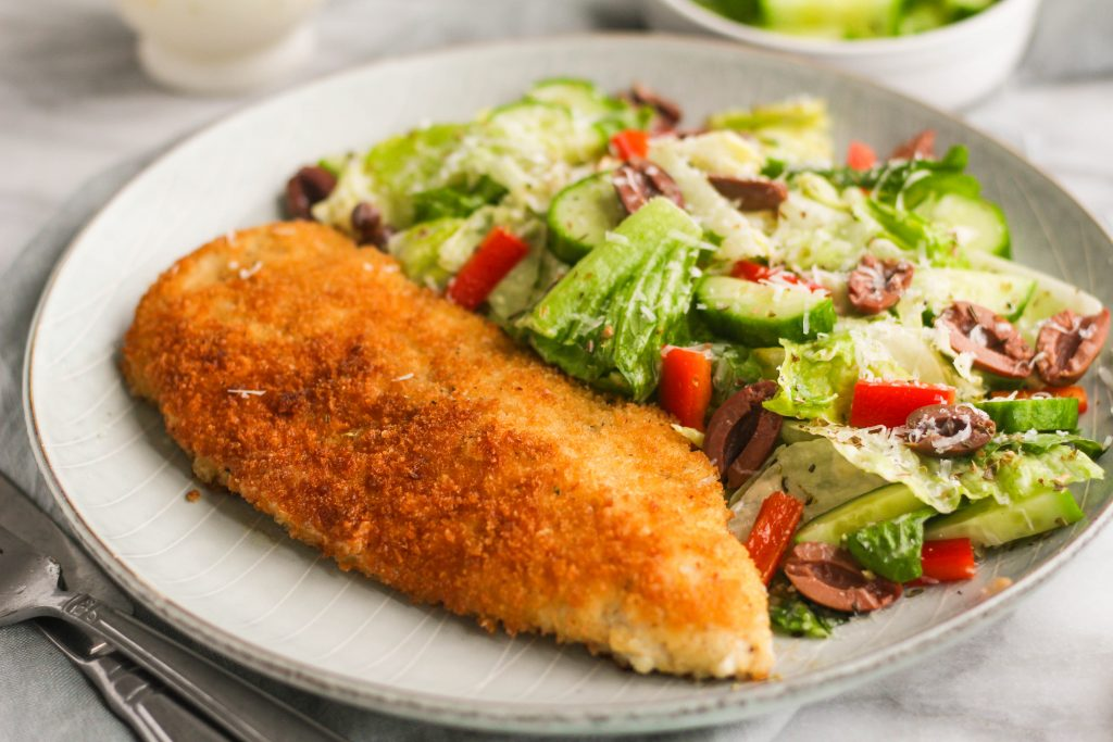 Chicken Milanese - a simple Panko breaded chicken breast, pan-fried in olive oil until golden brown. Served alongside a tangy creamy Italian style salad with crunchy peppers, cucumber, and olives.
