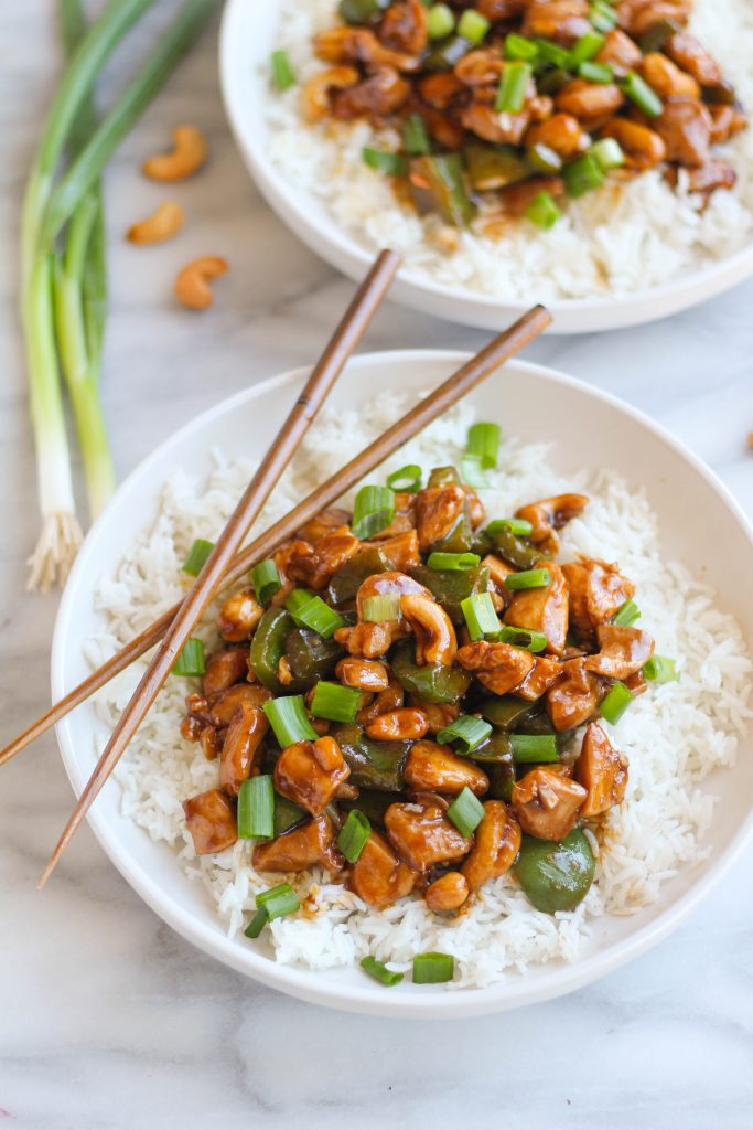 Savory and salty Cashew Chicken is very easy to throw together any night of the week! Chicken thigh bits combined with tender green bell peppers, crunchy cashews, and plenty of fresh green onions all served on a bed of white rice.