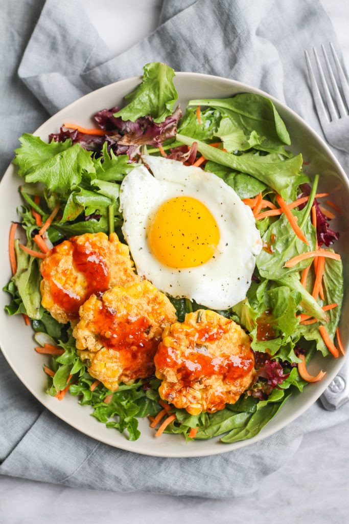 Sweet corn combined with Parmesan, chives, cornmeal, and a touch of flour formed into patties and pan-fried until golden. Pairs perfectly with a simple salad with vinegar dressing and a sunny-side-up egg.