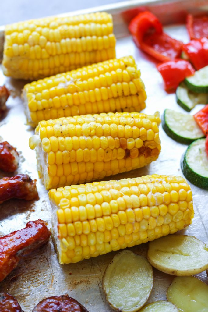 Create an entire barbecue dinner using just two baking sheet pans in under an hour! This recipe utilizes a stair-step method, meaning once the first item is in the oven (chicken), you'll prep the second item and place in the oven (and so on). Fresh corn on the cob, tender buttery baby potatoes, roasted zucchini, and bell pepper pair deliciously with bourbon barbecue sauced wings and sausage.